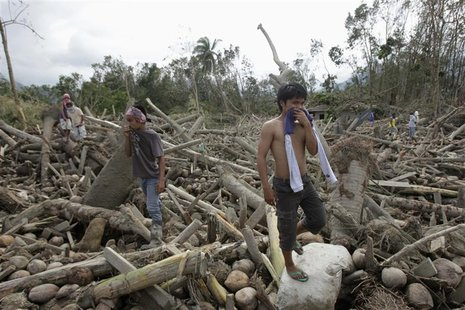 Residents search for their missing relatives among debris swept by floodwaters at the height of Typhoon Bopha, in New Bataan town in Compost