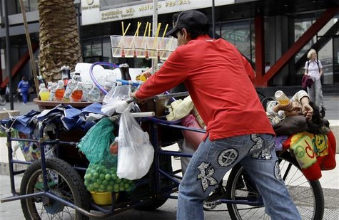 A street vendor selling soft drinks pushes his tricycle while his son lies on it on a street near the Zocalo main square in Mexico City July