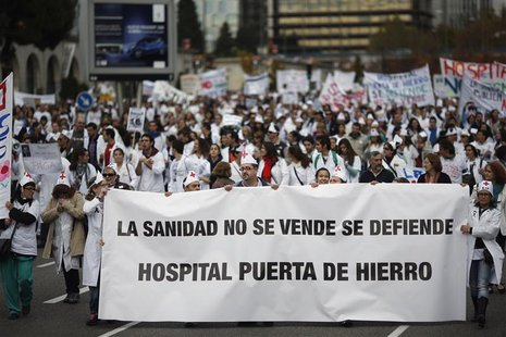 "Demonstrators march behind a banner that reads: ""Healthcare is not for sale, we have to defend it. Puerta de Hierro hospital"" during a prote"