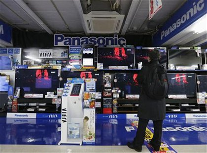 A man looks at Panasonic TV sets at an electronic shop in Tokyo November 22, 2012. Ratings agency Fitch cut the debt ratings of Japanese con