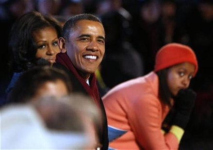 U.S. President Barack Obama (C) is joined by his daughter Malia (R) and first lady, Michelle Obama (L) as they watch the show at the officia