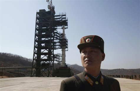 A soldier stands guard in front of a rocket sitting on a launch pad at the West Sea Satellite Launch Site, during a guided media tour by Nor