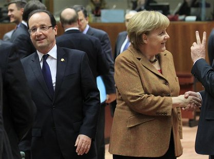 France's President Francois Hollande (L) walks past Germany's Chancellor Angela Merkel during a summit of European Union leaders discussing