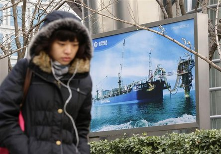 A woman walks past a poster showing an offshore work platform from the China National Offshore Oil Corp (CNOOC) next to its headquarters bui