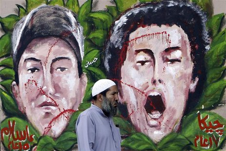 An anti-Mursi protester walks past graffiti depicting two activists who died recently, at Tahrir Square in Cairo December 10, 2012. REUTERS/