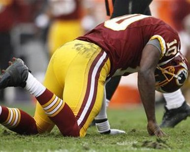 Washington Redskins quarterback Robert Griffin III gets up slowly after being tackled by the Baltimore Ravens defense in the first half of their NFL football game in Landover, Maryland December 9, 2012. This is not the play in which Griffin III left the game.  REUTERS/Gary Cameron