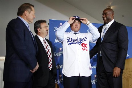 Los Angeles Dodgers' new left-handed pitcher Hyun-Jin Ryu of South Korea (2nd R) wears a cap as he puts on his new jersey while standing wit