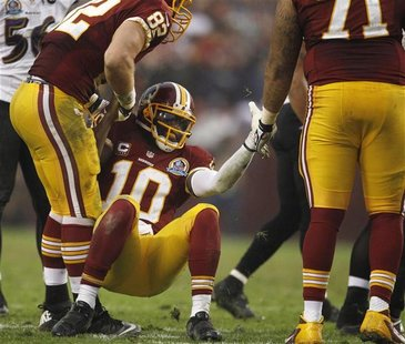 Washington Redskins quarterback Robert Griffin III (C) is helped up by teammates after being tackled by the Baltimore Ravens defense in the