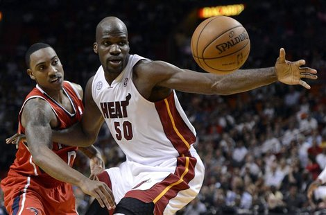 Miami Heat's Joel Anthony (R) and Atlanta Hawks' Jeff Teague (L) fight for a loose ball during the first half of their NBA basketball game i