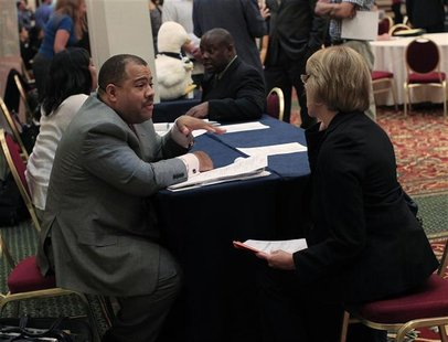 A job recruiter speaks with a woman during a job fair in Melville, New York July 19, 2012. REUTERS/Shannon Stapleton