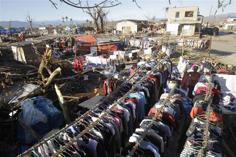 Residents hang clothes they are selling to dry under the sun in the coastal town of Cateel that was devastated during last Tuesday's Typhoon