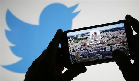 Pope Benedict XVI's twitter account is pictured on a smart phone in front of the Twitter logo displayed on a laptop in this photo illustrati