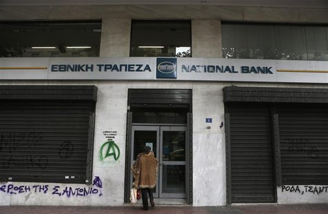 A woman stands outside a National bank branch in central Athens December 11, 2012. REUTERS/John Kolesidis