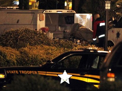 An Oregon State Medical Examiner loads a body into a van at the Clackamas Town Center shopping mall in Portland, Oregon December 11, 2012. A
