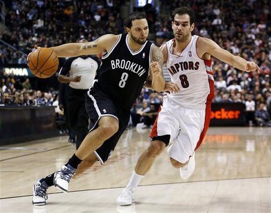 Brooklyn Nets Deron Williams drives to the net past Toronto Raptors Jose Calderon during the second half of their NBA basketball game in Tor