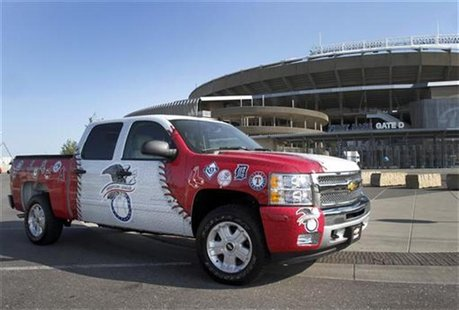 A 2013 Chevrolet Silverado pickup truck, painted with logos of both American League and National League teams, is pictured in front of Kauff