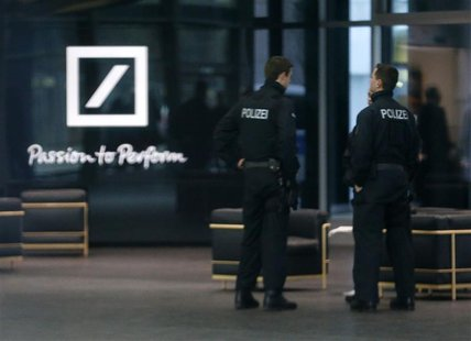 Police officers stand inside the lobby of the headquarters of Germany's largest business bank, Deutsche Bank AG in Frankfurt December 12, 20