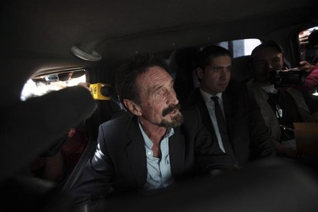 Software pioneer John McAfee is escorted by immigration officers at La Aurora International Airport in Guatemala City December 12, 2012. REU