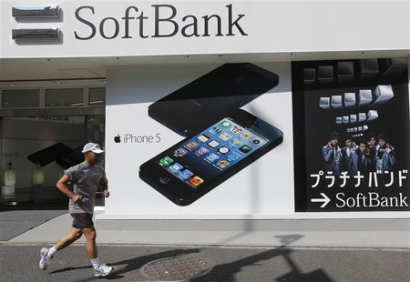 A jogger runs past a Softbank shop in Tokyo October 16, 2012. Softbank Corp's pricey $20 billion (12 billion pounds) bid to buy control of N