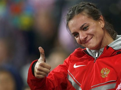 Russia's Yelena Isinbayeva gives a thumbs-up after winning bronze in the women's pole vault final during the London 2012 Olympic Games at th