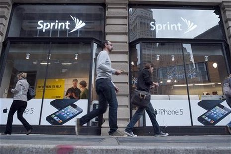 Passers-by walk past a Sprint store in New York, October 15, 2012. REUTERS/Keith Bedford