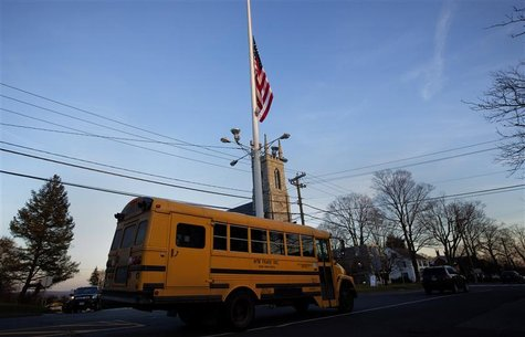 A flag is seen at half mast as a school bus passes along Main Street in Newtown, Connecticut December 14, 2012. REUTERS/Shannon Stapleton