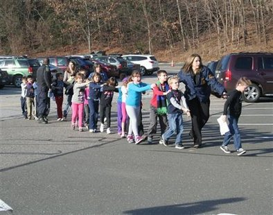 State police personnel lead children from the Sandy Hook Elementary School in this handout picture from the Newtown Bee, in Newtown, Connecticut, December 14, 2012. All public schools in Newtown, Connecticut, were placed in lockdown on Friday following a shooting at Sandy Hook Elementary School. Credit: Reuters/Newtown Bee/Shannon Hicks/Handout
