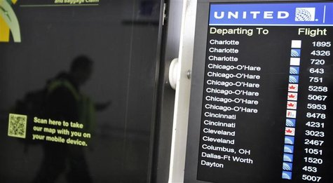 A customer is reflected in a screen showing the schedule times of United Continental Holdings Inc flights at Newark International airport in
