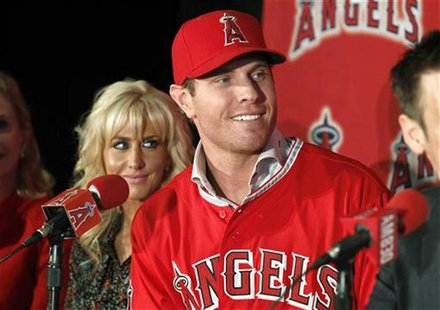 Los Angels Angels newly acquired outfielder Josh Hamilton talks with reporters as his wife, Katie, looks on during a news conference at the