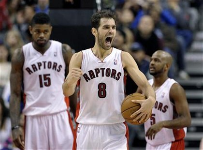 Toronto Raptors guard Jose Calderon (C) reacts in front of teammates Amir Johnson (L) and John Lucas III after drawing a penalty to the Hous