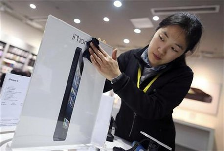 An employee cleans an advertisement plate at an Apple dealership on the eve of iPhone 5's release, in Wuhan, Hubei province December 13, 201