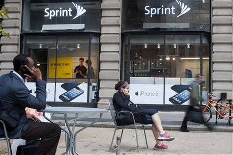 People talk on their cell phones as passers-by walk past a Sprint store in New York, October 15, 2012. REUTERS/Keith Bedford