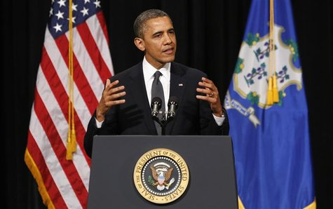 U.S. President Barack Obama gestures as he speaks at a vigil held at Newtown High School for families of victims of the Sandy Hook Elementar