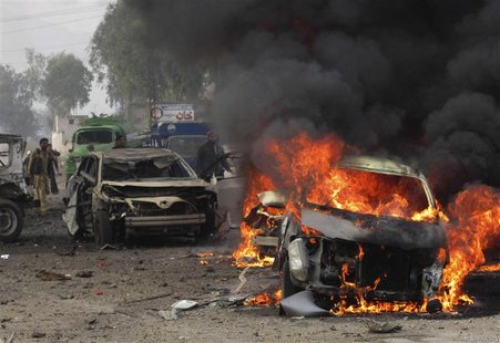 A police officer and a citizen walk towards a burning car after a bomb attack, at Fauji Market in Peshawar December 17, 2012. REUTERS/Ameerz