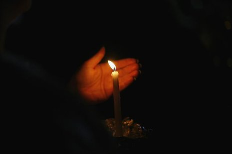 People light candles at a makeshift memorial for the victims of the Sandy Hook Elementary School shooting in Newtown, Connecticut December 1