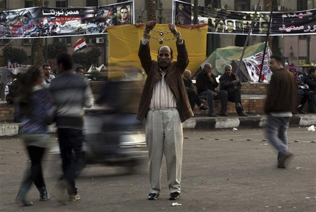 A man holds up chained hands as he protests against Egypt's President Mohamed Mursi at Tahrir Square in Cairo December 17, 2012. REUTERS/Amr