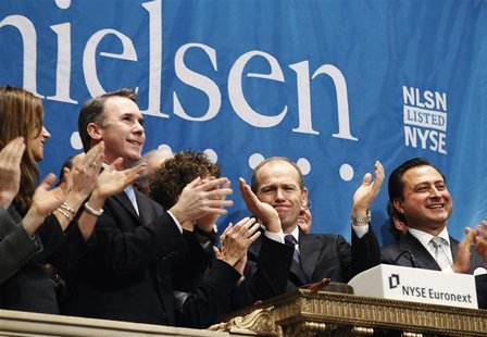 Nielsen CEO, David Calhoun, (2nd R) and company officials ring the opening bell at the New York Stock Exchange in celebration of their IPO,