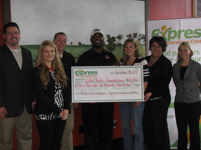 LeRoy Butler accepts the $15,221 check on behalf of his foundation to help these women in need.