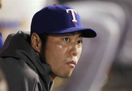 Texas Rangers relief pitcher Koji Uehara of Japan, who is currently on the disabled list, sits in the dugout against the Los Angeles Angels