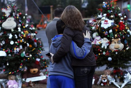 A woman embraces a boy next to a makeshift memorial for victims who died in the December 14 shootings at Sandy Hook Elementary School, in Ne