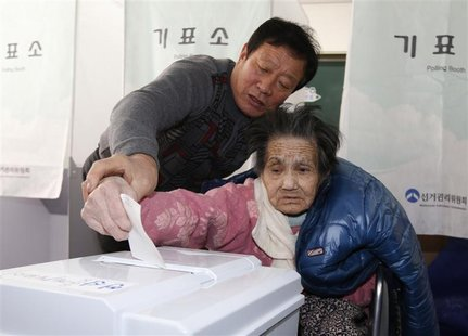 An elderly woman is assisted in casting her ballot in the presidential election at a polling station in Nonsan, about 190 km (118 miles) sou