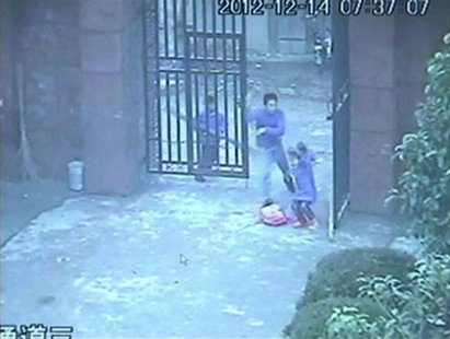 A man (C), waving a knife in his hand, chases a girl (R) as he enters an elementary school in Guangshan county, Henan province, in this stil