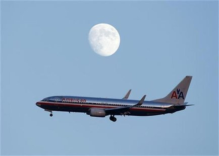 An American Airlines passenger jet glides in under the moon as it lands at LaGuardia airport in New YorkNew York, August 28, 2012. REUTERS/E