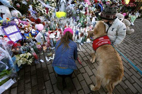 "Four-year-old Brody Sauli of Newtown, Connecticut hugs a volunteer service ""comfort"" dog as his sister Amanda kneels to light candles at a g"