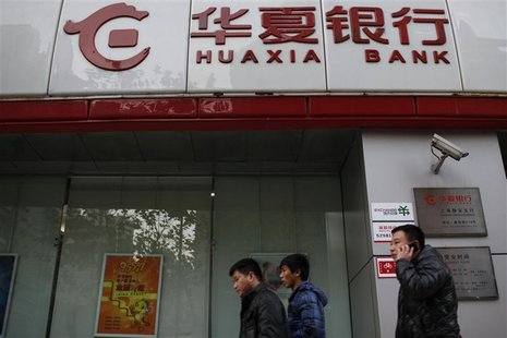 Locals walk past a Huaxia Bank in Shanghai, December 12, 2012. Picture taken December 12, 2012. REUTERS/Aly Song