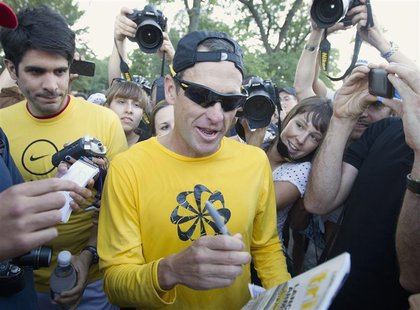 Lance Armstrong (C) signs autographs following a run with his fans at Mount Royal park in Montreal August 29, 2012. REUTERS/Christinne Musch