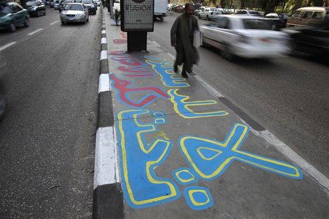 "A man walks on a graffiti on a pavement in Cairo December 20, 2012. The graffiti reads, ""No to the constitution under the rule of the (Musli"