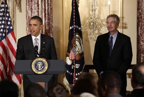 U.S. President Barack Obama delivers remarks next to Deputy Secretary of State William Burns at the Diplomatic Corps holiday reception at th