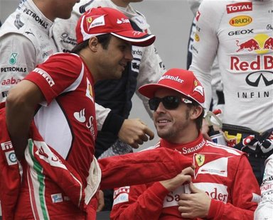 Ferrari Formula One driver Felipe Massa of Brazil (L) and team mate Fernando Alonso of Spain get ready for a group photo before the Brazilia