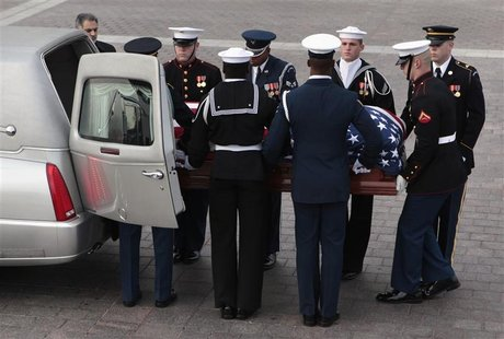 A military honor guard carries the casket of Senator Daniel Inouye (D-HI) as it arrives on Capitol Hill in Washington December 20, 2012. REU